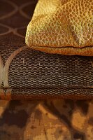 Gold, spotted cushion on folded blanket with ethnic pattern