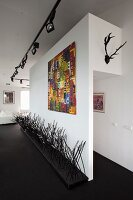 Objets d'art on black floor, colourful modern artwork on wall and lighting system with spotlights on black rails