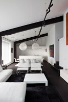 White designer furniture and low coffee table on black rug with dining area and kitchen in background in loft apartment