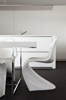 White Panton chairs at table with chrome frame in front of free-standing, designer kitchen counter