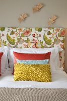Scatter cushions on double bed with floral headboard below wooden bird figurines on wall