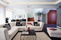 Elegant, pale corner couch and coffee table on flokati-style rug in open-plan interior with indirect ceiling lights