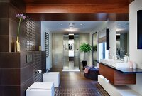 Elegant designer bathroom - custom washstand, bathroom fittings on brown-tiled wall and shower area
