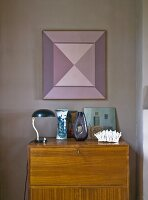 Table lamp and blue and white vase on bureau below geometric artwork on mauve wall