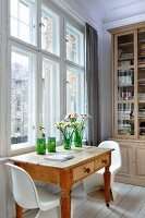 Wooden table with drawers and white Panton chairs in front of bookcase in traditional, period interior