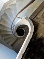 View down stairwell with spiral balustrade and concrete spiral staircase