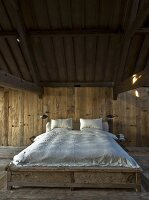 Double bed with white bed linen in minimalist, wood-clad bedroom with rustic ambiance