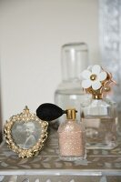 Vintage-style perfume bottles and frames photo on dressing table