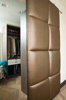 Open, upholstered sliding door with brown, shimmering cover and view into dressing room