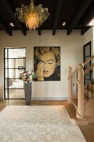 Entrance hall with extravagant pendant lamp hanging from wooden ceiling, portrait of Marilyn Monroe on wall and bouquet in floor vase