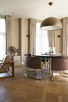 Designer chairs around a round table in a room decorated in shades of beige