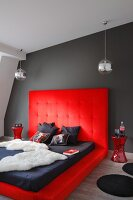 Dramatic bedroom; animal-skin blanket and mattress on platform upholstered in red with tall headboard against dark grey wall
