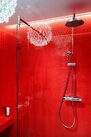 Rainfall shower and hand-held shower head on red tiled wall with reflection of pendant lamp
