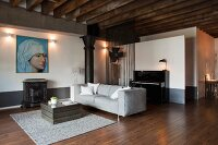 Antique stove below large Renaissance portrait in lounge area of loft apartment with rustic wood-beamed ceiling