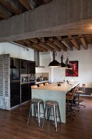 Dining counter with bar stools and two classic metal bar stools at one end in loft apartment with rustic wood-beamed ceiling