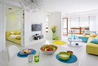 White, open-plan interior with various splashes of colour, dining table, open sliding doors and view into bedroom