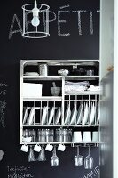 Stainless steel, wall-mounted crockery rack on chalkboard wall