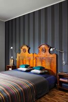 Bed with antique wooden headboards against striped wallpaper