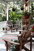 Wooden armchair on terrace with white-painted wooden floor, white balustrade, hanging baskets and tropical garden in background