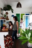 Mother an daughter stood next to kitchen counter; foliage plant in glass vase in foreground