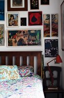 A bed with a wooden slatted headboard, ethnic patterned bedclothes and a collection of pictures on the wall