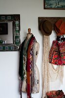 Ties draped over a vintage tailors dummy standing between a mirror and a coat rack with hats on the wall