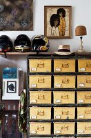 Vintage apothecary cabinet with yellow-painted fronts and handles and rustic wooden frame below several motorbike helmets on shelf