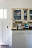 Vintage-style crockery on and in white-painted kitchen dresser