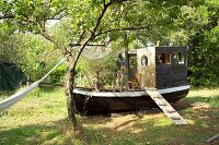 Wooden hut built on old boat in garden