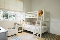 White bunk beds and bedside cabinet below window in children's bedroom