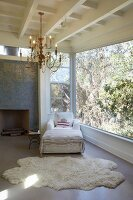 White animal-skin rug, armchair and ottoman next to panoramic window and below vintage chandelier hanging from wooden ceiling