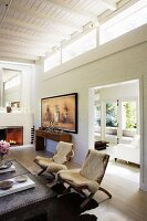 Chairs with white sheepskin blankets, wide, open doorway and clerestory windows in living room with white, wooden ceiling
