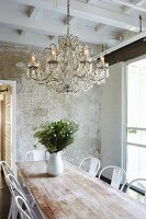Dining set with classic chairs, bouquet in white jug and chandelier hung from wooden ceiling