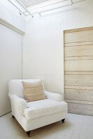 Traditional armchair with white upholstery in corner of room with white-painted brick walls