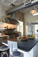 Vintage, metal bar stools at counter with black stone worksurface below ventilation duct in open-plan kitchen
