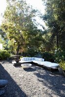 Corner bench with white cushions and fire bowl on sunny, gravel terrace in garden