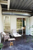 Terrace furnished with wicker chair, stool and small table outside contemporary house with ventilation duct running below corrugated metal ceiling