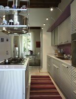 Kitchen with corrugated metal fronts and purple back wall; extractor hood with integrated glass shelves above island counter with hob
