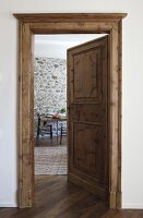 Traditional panelled door and door frame and view of dining area against stone wall