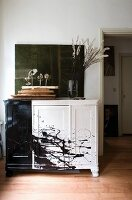 Branches of white flowers in glass vase on artistically painted black and white cabinet in corner of interior with traditional character
