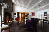 Open-plan, eclectic interior of loft apartment with modern sofa, Rococo armchair and open fireplace