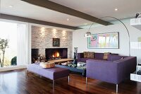 Elegant, purple sofa set in lounge area with arc lamp and cosy open fire in stone wall