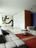 Grey sofa set and retro side table in lounge area; dining area next to partition cupboards in open-plan interior