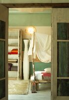 Rustic bedroom; tall floor vase next to bed with improvised fabric canopy