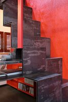 Metal samba staircase leading up red wall