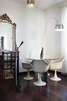 Tulip armchairs, vintage glass table and classic arc lamp next to shelves of CDs and antique mirror