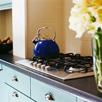Kettle on hob and flowers on counter