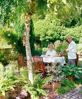 Man and woman at set table with teak chairs in summery garden