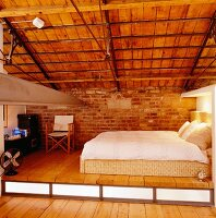 Attic bedroom on platform beneath exposed roof beams and trusses