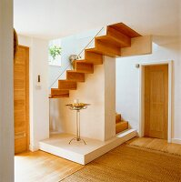 Candles on delicate table under wooden staircase